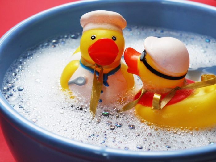 two rubber ducks in bowl of water