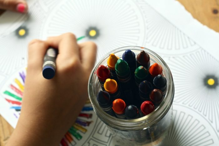 crayons with child colouring in