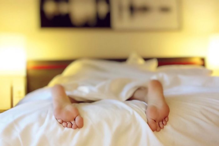 person in bed with feet poking out of duvet