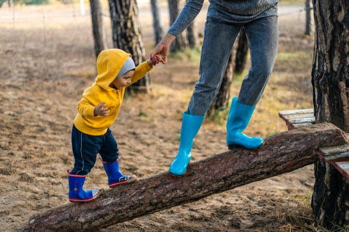 Toddler and adult in wellies climbing a log