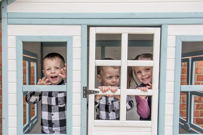 children smiling in playhouse
